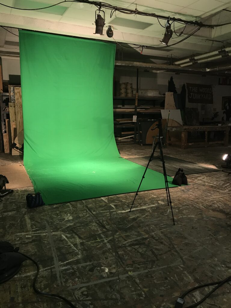 Green fabric with theater lighting and a tripod in front of it